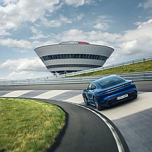 Ein fahrender blauer Porsche Taycan auf der Porsche Leipzig Rundstrecke.