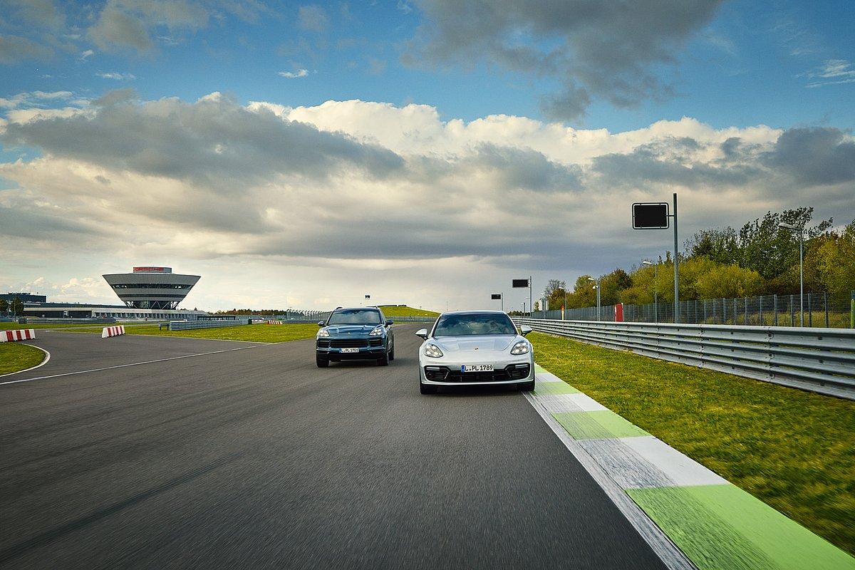 Ein dunkelblauer Porsche Cayenne und ein silberner Porsche Panamera auf der Porsche Leipzig Rundstrecke.